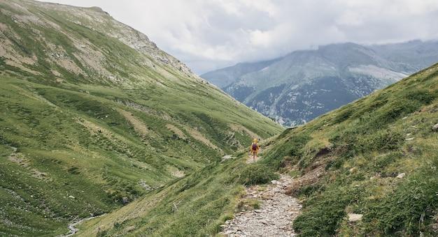 Vista de um alpinista caminhando em um caminho entre as montanhas