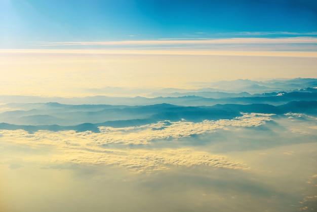 Vista de um avião ao pôr do sol no céu com raios solares. fundo de nuvens fofas