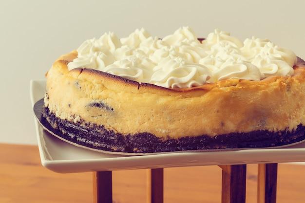 Vista de um biscoito preto e bolo de creme em uma parede branca