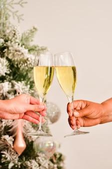 Vista de um brinde com taças de champanhe sendo feito por duas mãos femininas