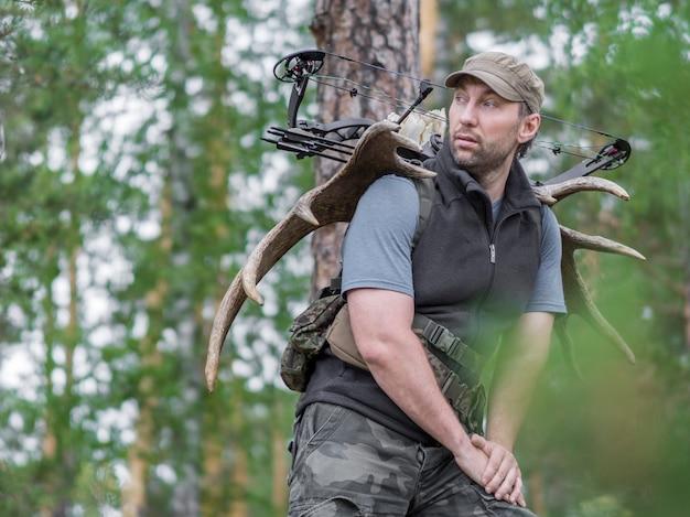 Vista de um caçador na floresta de verão com um arco na floresta carrega chifres de alce nas costas