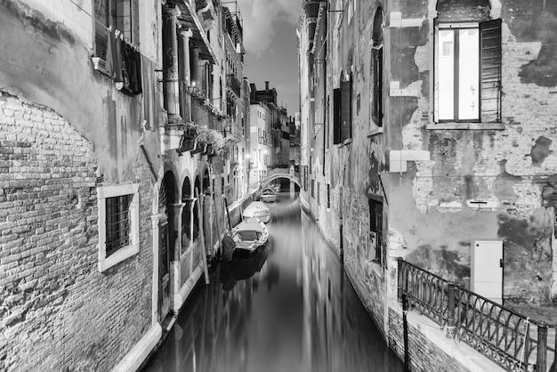 Vista de um canal pitoresco e uma pequena ponte à noite no bairro de santa croce em veneza, itália