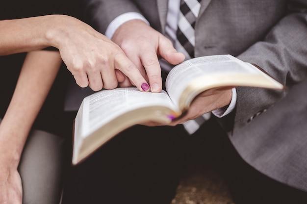 Vista de um casal lendo um livro juntos enquanto aponta uma parte em uma página