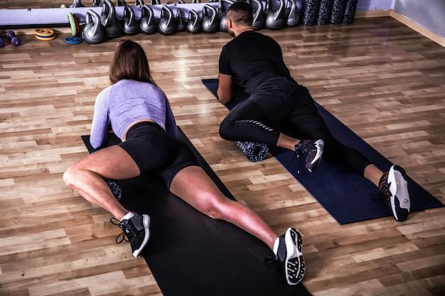Vista de um casal musculoso fazendo exercícios de tábuas