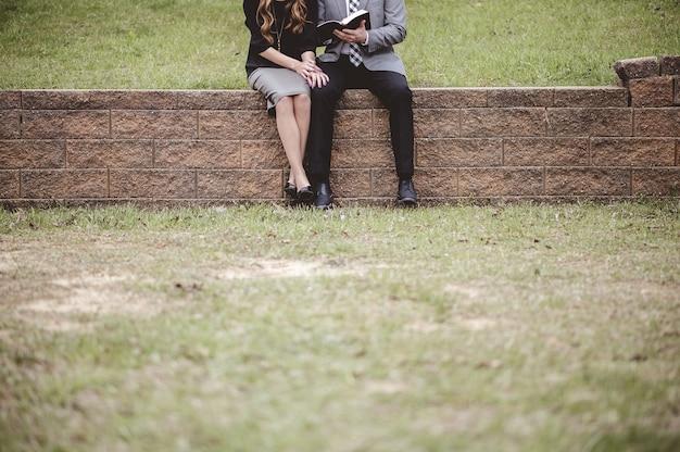 Vista de um casal usando roupas formais, lendo e discutindo um livro enquanto está sentado em um jardim