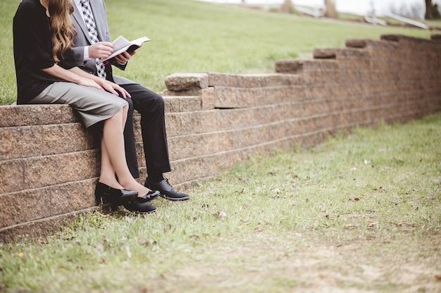 Vista de um casal vestindo roupas formais e lendo um livro sentado em um jardim