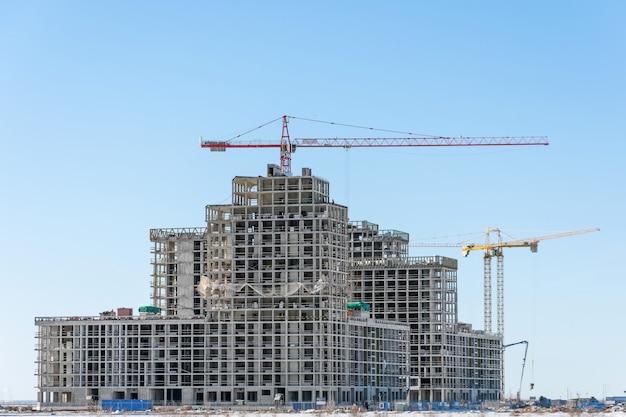 Vista de um complexo residencial em construção com guindastes altos. edifício em larga escala da cidade