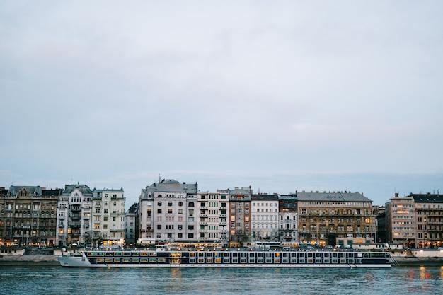 Vista de um enorme navio navegando no rio danúbio contra o fundo de edifícios em budapeste