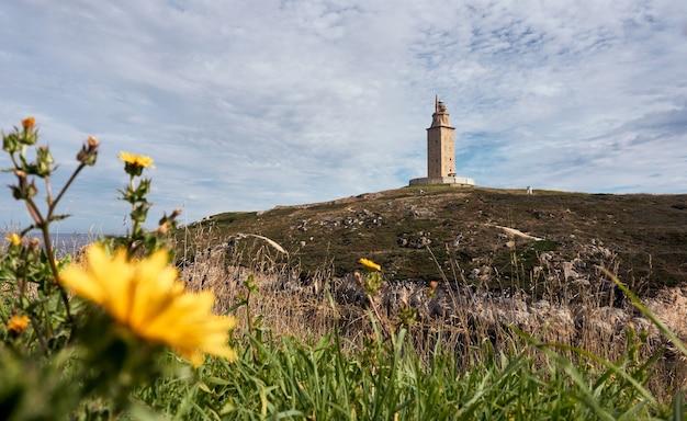 Vista de um farol no topo da montanha com flores. torre de hércules