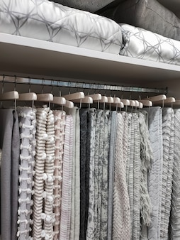 Vista de um guarda-roupa com cobertores de lã pendurados em cabides e travesseiros e cobertores nas prateleiras.
