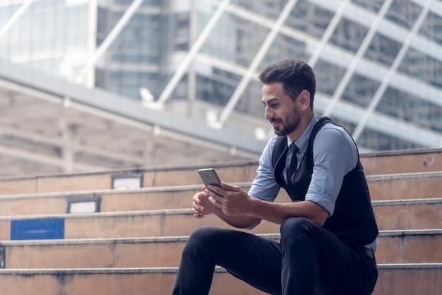 Vista de um homem de negócios atraente jovem usando smartphone