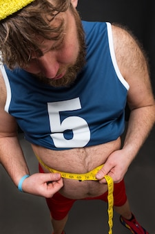 Vista de um homem gordo medindo a barriga sobre o cinza