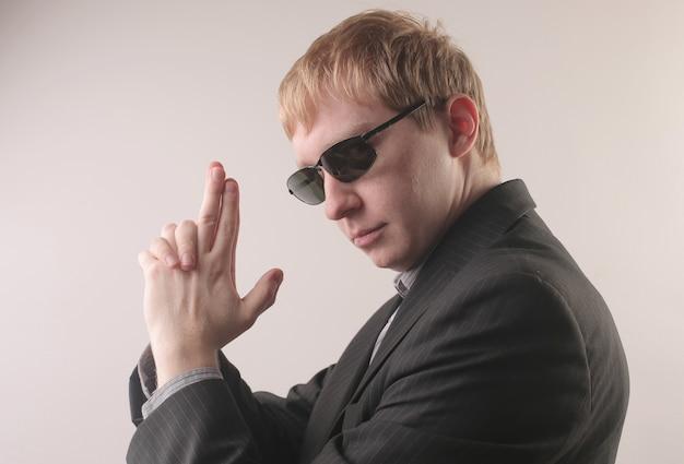 Vista de um homem vestindo um terno preto e óculos escuros enquanto faz a posição de uma arma com os dedos