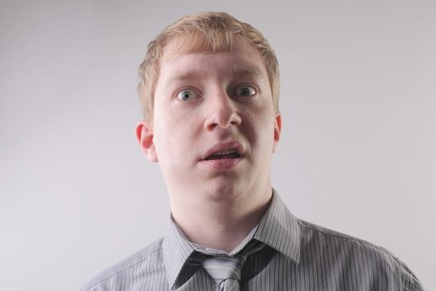 Vista de um homem vestindo uma camisa cinza com uma expressão facial de medo