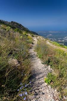 Vista de um longo caminho de cascalho na alta montanha em um dia ensolarado