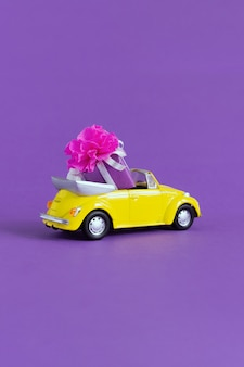 Vista de um pequeno carro amarelo colorido em que há uma caixa de presente com um laço em um roxo. feriado do conceito, transporte, dia dos namorados, brinquedos