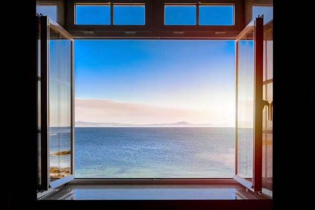 Vista de um quarto escuro no mar durante o pôr do sol através de uma janela aberta