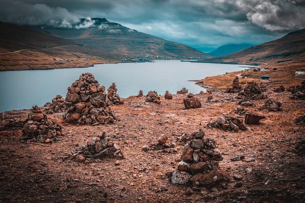 Vista de um rio e várias pilhas de pedras na estrada para saksun