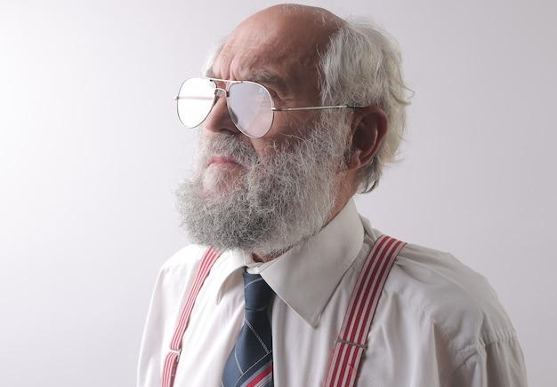 Vista de um velho homem caucasiano com óculos, olhando para longe - conceito: preocupado, pensando