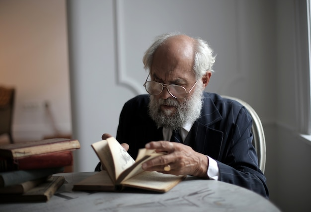 Vista de um velho homem caucasiano lendo um livro antigo em uma sala