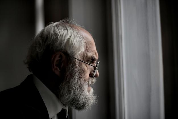 Vista de um velho homem caucasiano olhando pela janela