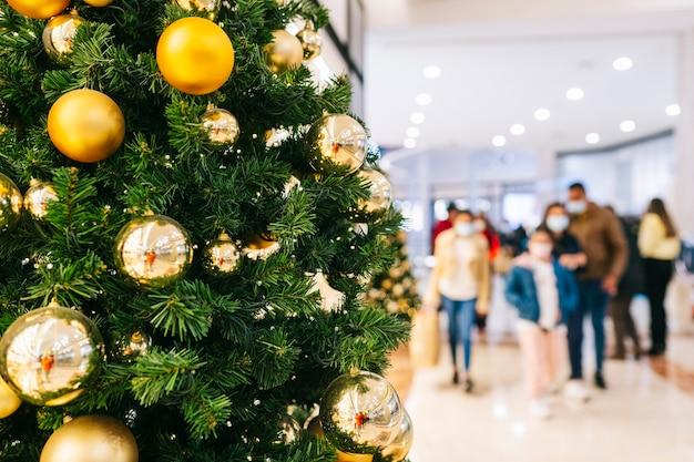 Vista de uma árvore de natal em primeiro plano com o fundo desfocado de um shopping center