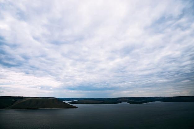 Vista de uma baía e litoral distante com nuvens escuras
