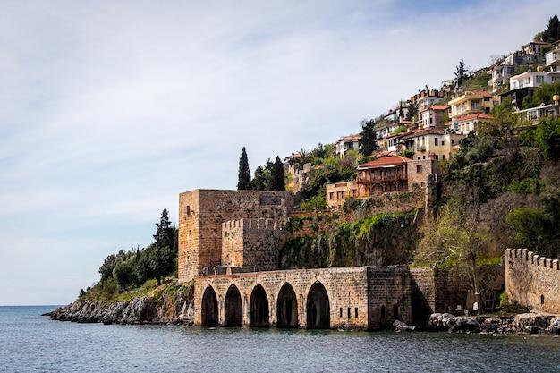 Vista de uma bela cidade medieval situada em uma colina com vista para o mar. estaleiro e arsenal em alanya em um dia ensolarado, turquia