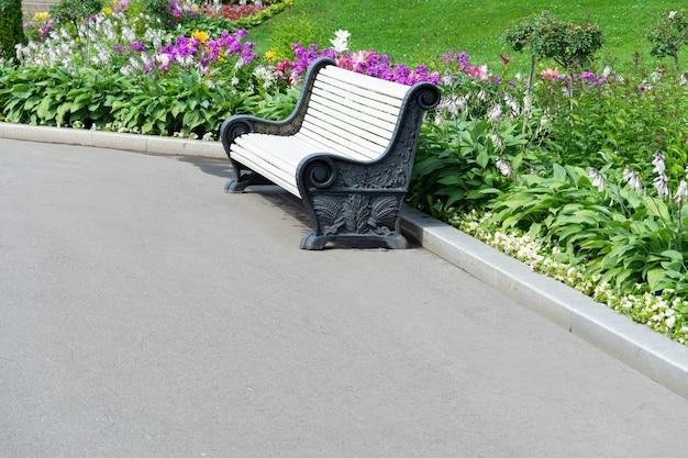 Vista de uma benche no parque, o gramado e as flores