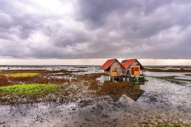 Vista de uma casa abandonada no meio do lago com céu e chuva ao pôr do sol