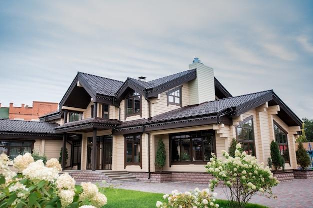 Vista de uma casa moderna luxuosa com elementos decorativos ao redor das janelas e jardim da frente com flores brancas desabrochando