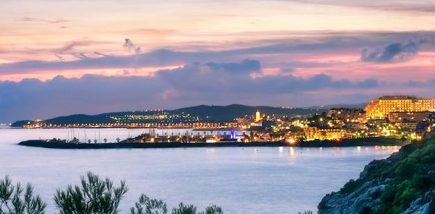 Vista de uma cidade costeira ao pôr do sol