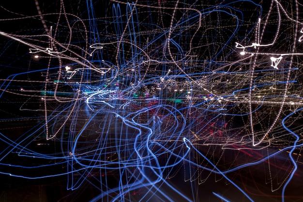 Vista de uma composição abstrata de luzes obscuras na rua movendo ou agitando a câmera.