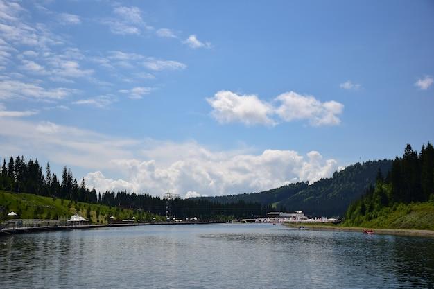 Vista de uma estação de veraneio nas montanhas com um grande lago e lugares confortáveis para recreação e passeios ao longo de suas margens. contra o pano de fundo de montanhas arborizadas e céu azul