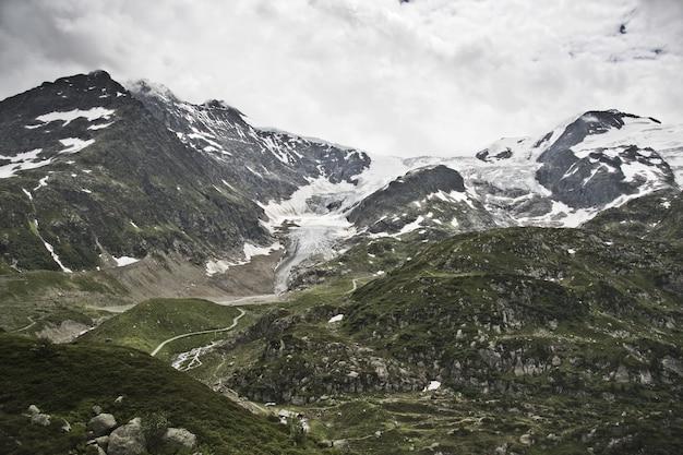 Vista de uma estrada estreita cercada por altas montanhas cobertas de neve no topo