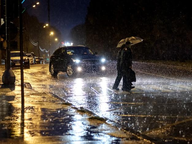 Vista de uma faixa de pedestres na cidade à noite durante uma forte chuva, silhuetas de pessoas com guarda-chuvas