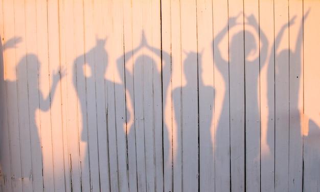 Vista de uma foto do divertimento de um grupo de amigos que fazem as poses que criam uma sombra em uma parede de madeira.