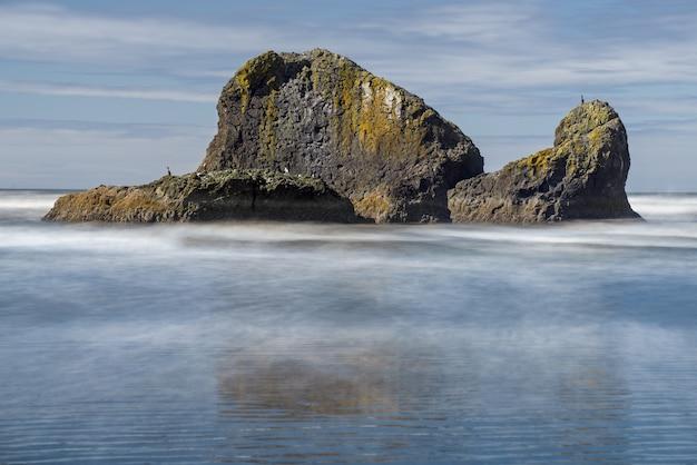 Vista de uma ilha misteriosa com seu reflexo na superfície do mar em um dia nublado.
