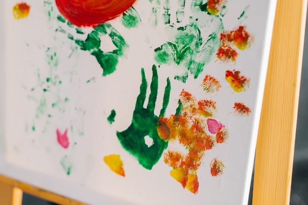 Vista de uma impressão da mão em uma folha de papel. mãos manchadas de tintas coloridas.