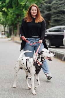 Vista de uma jovem mulher caucasiana caminhando pela cidade durante o período da manhã com um cachorro dálmata
