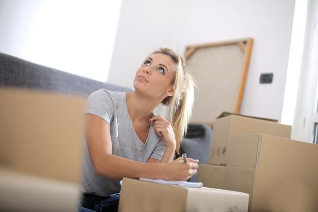 Vista de uma linda mulher branca, escrevendo em um caderno, cercada de caixas