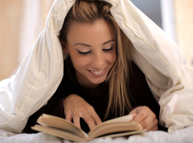 Vista de uma linda mulher branca lendo um livro sob um cobertor branco