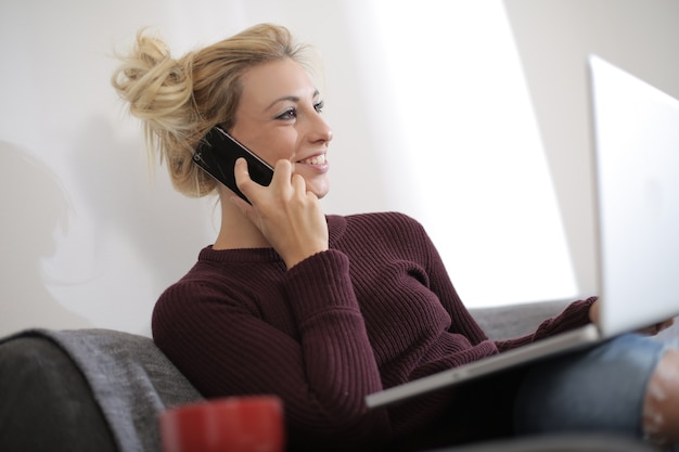 Vista de uma linda mulher branca, sentada no sofá, enquanto trabalhava no laptop e conversava