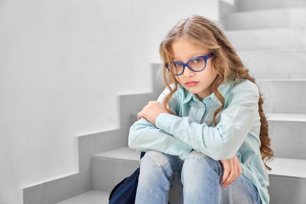 Vista de uma menina bonita da escola com cabelo longo cacheado, sentada sozinha no corredor da escola e ofendida, olhando para a câmera.