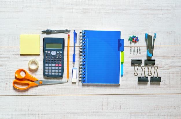 Vista de uma mesa de madeira com um caderno, caneta, lápis, borracha, tesoura, fita adesiva, pinças, grampeador, clipes, alfinetes e uma calculadora em uma boa ordem