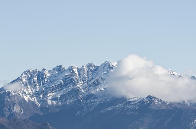Vista de uma montanha rochosa coberta de neve parcialmente coberta por nuvens
