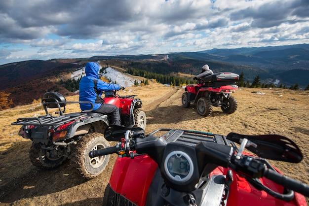 Vista de uma moto-quatro com homens dirigindo um atv em frente no topo da trilha de montanha