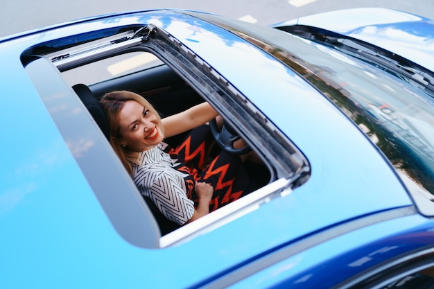 Vista de uma mulher dirigindo pelo teto solar