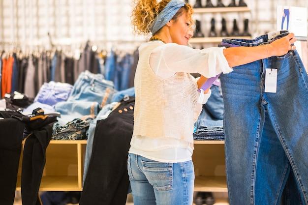 Vista de uma mulher urbana caucasiana na moda escolhendo e procurando uma calça jeans dentro de uma loja da moda - conceito de compras e consumismo para as pessoas - comércio de roupas casuais