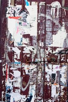Vista de uma parede embarcada de madeira com papel de publicidade torned.
